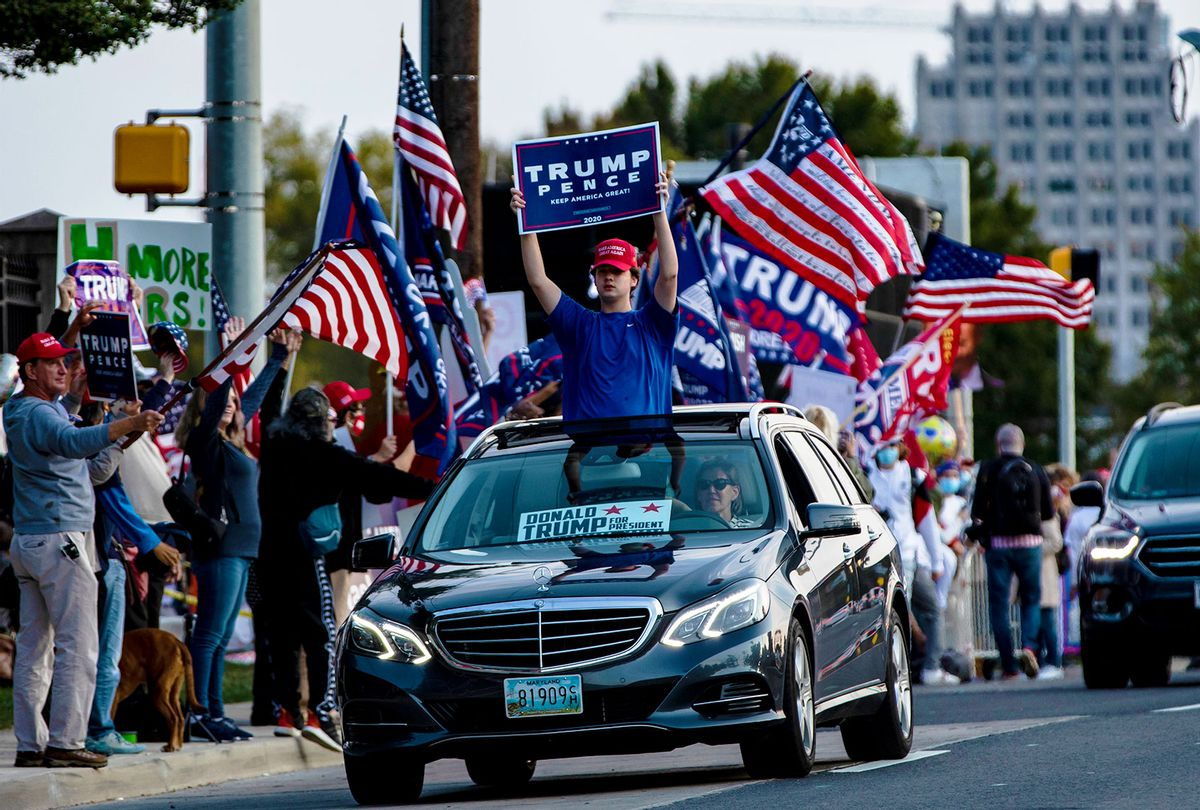 A supporter of President Donald Trump holds a campaign sign through the moonroof of a car as they drive past Walter Reed National Military Medical Center after the President was admitted for treatment of COVID-19 on October 4, 2020 in Bethesda, Maryland. (Samuel Corum/Getty Images)