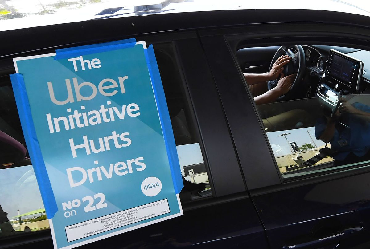 A ride share driver participates in a protest by drivers and their supporters, August 20, 2020 at Los Angeles International Airport in Los Angeles, California. - Rideshare service rivals Uber and Lyft were given a temporary reprieve on August 20 from having to reclassify drivers as employees in their home state of California by August 21. (ROBYN BECK/AFP via Getty Images)