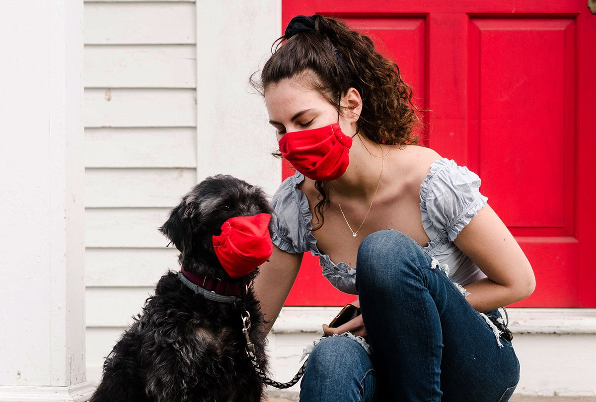 Young woman and dog wearing read mask during COVID-19 pandemic (Getty Images)