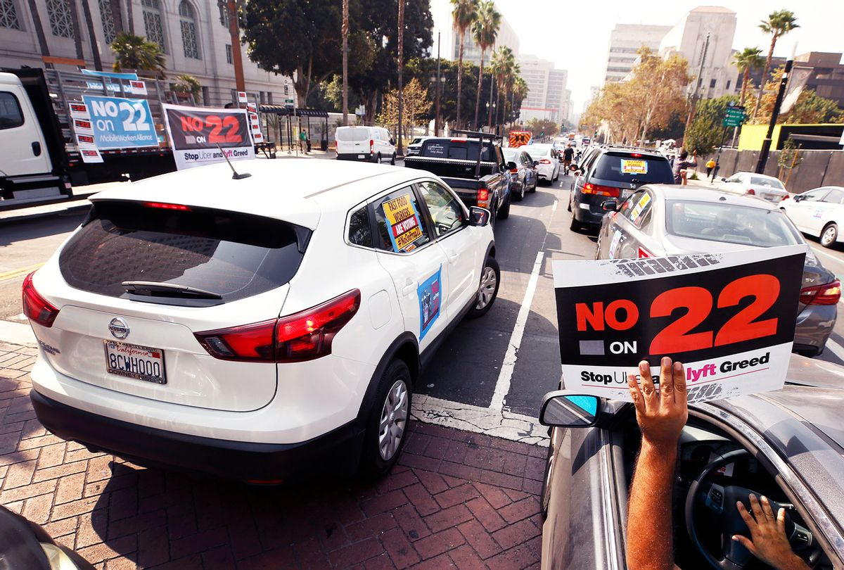 Rideshare driver Jorge Vargas raises his No on 22 sign in support as app based gig workers held a driving demonstration with 60-70 vehicles blocking Spring Street in front of Los Angeles City Hall urging voters to vote no on Proposition 22, a November ballot measure that would classify app-based drivers as independent contractors and not employees or agents, providing them with an exemption from Californias AB 5. (Al Seib / Los Angeles Times)