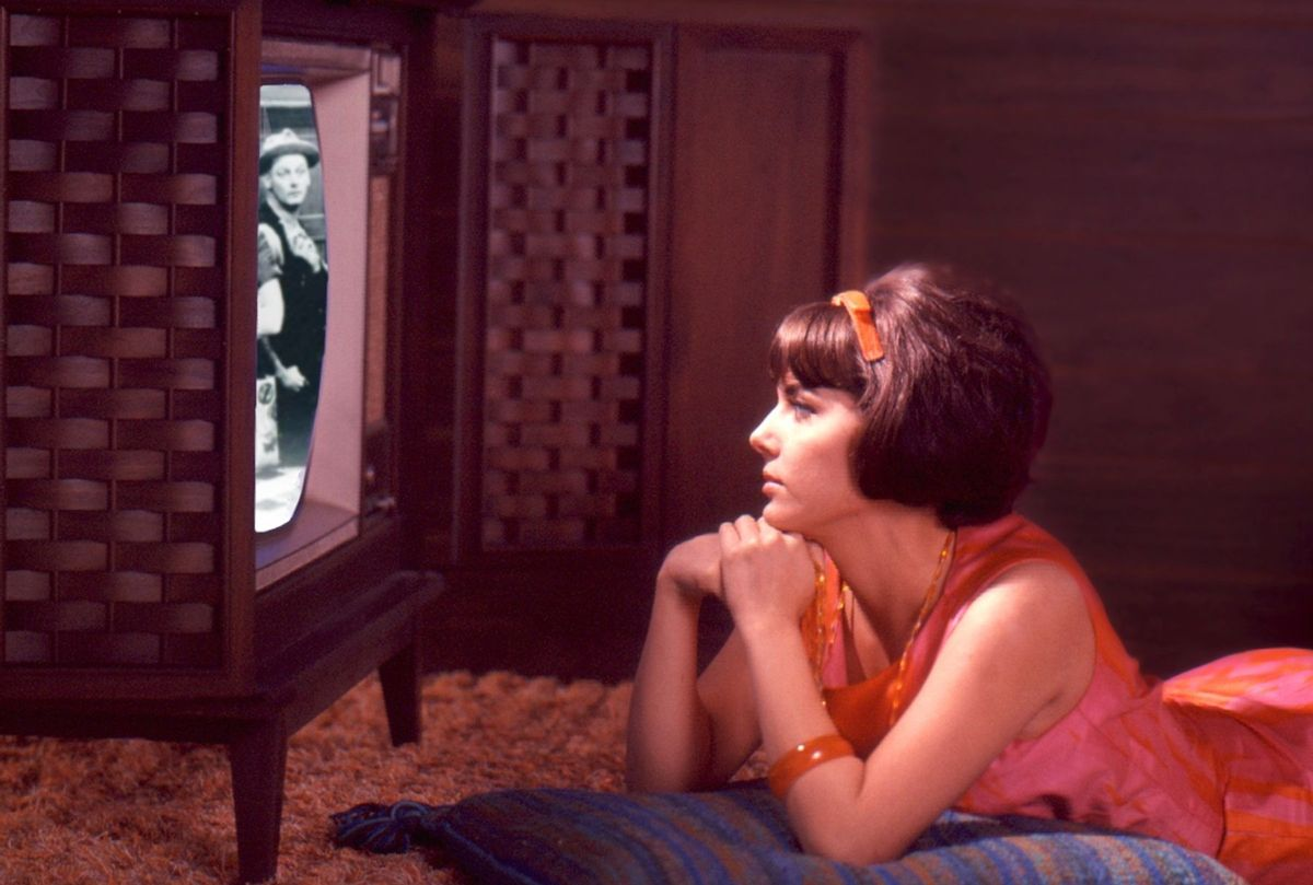 A composite image shows a young woman in a pink and orange dress lies on the floor and watches an episode of 'The Honeymooners' on a console television set, late 1960s or early 1970s. On the screen is an image of American actor Art Carney (1918 - 2003) (Tom Kelley/Getty Images)