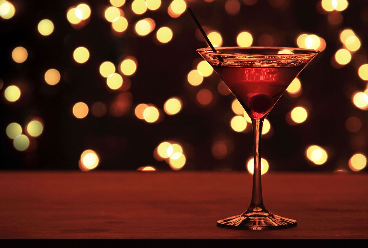 Christmas Cherry Martini on bar top counter with christmas lights in background (Getty Images)