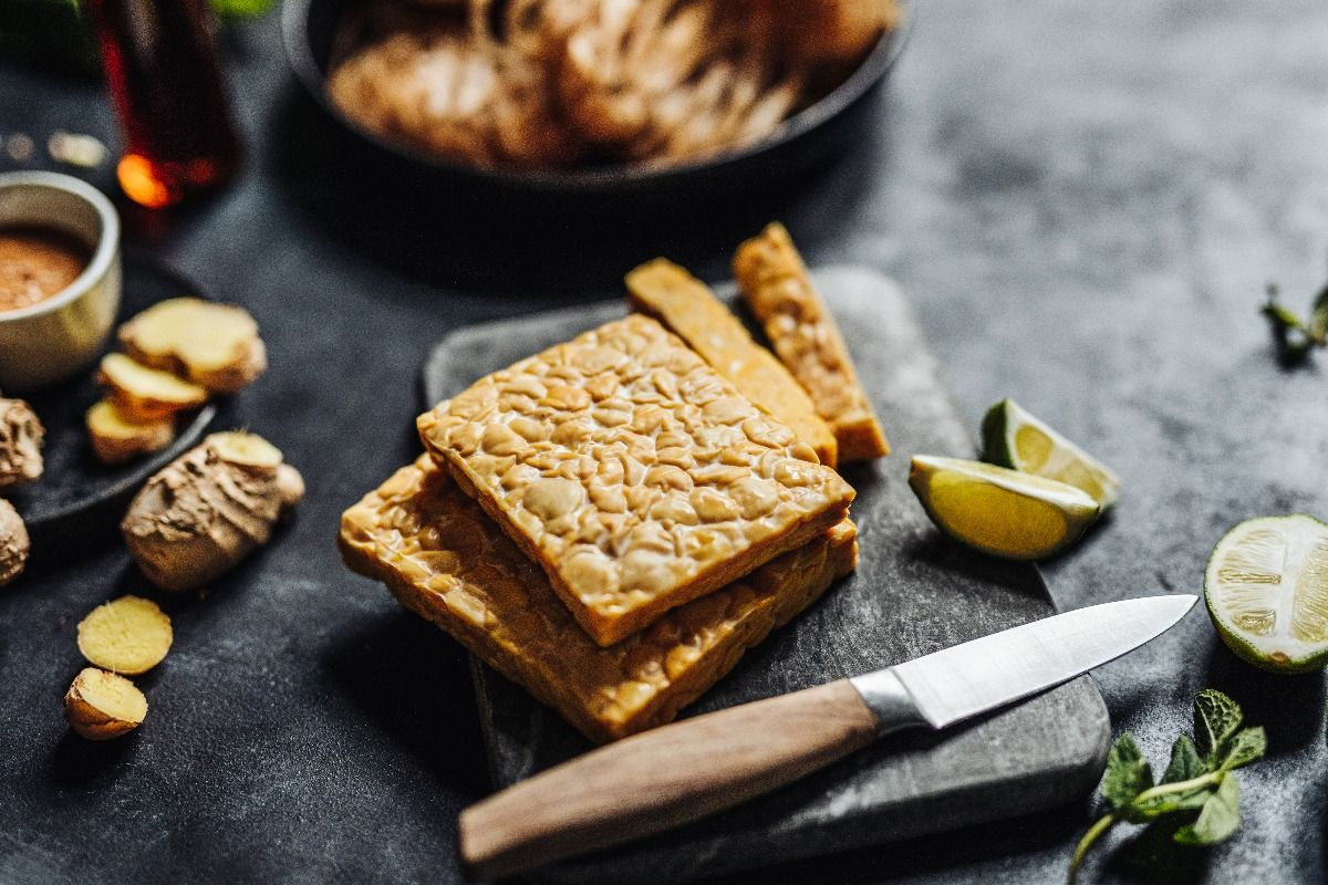 Close-up of tempeh on a cutting board with a kitchen knife with other ingredients. (Getty Images)
