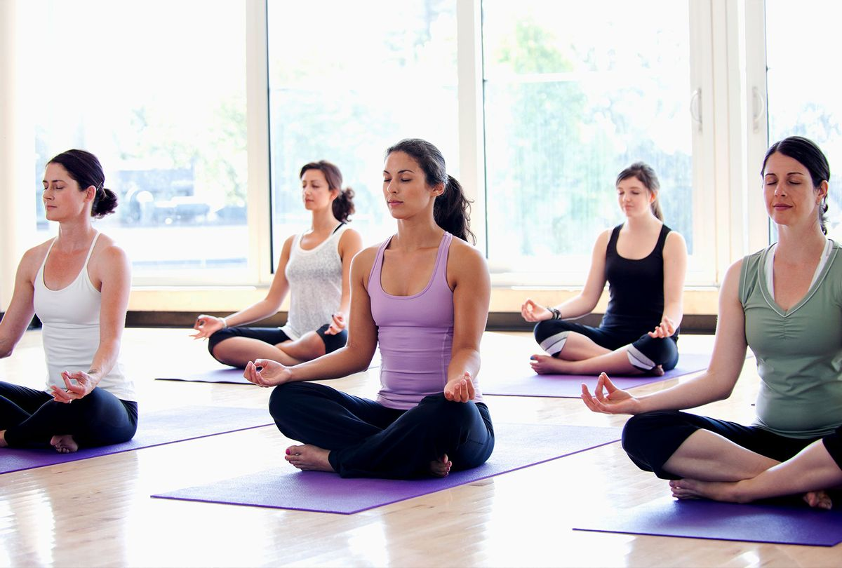 Class of women performing the meditative Sukhasana pose in a bright, modern yoga studio. (Getty Images)