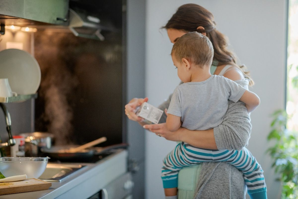 Mother with toddler on hip holding a carton of cooking cream and checking label. (Getty Images)