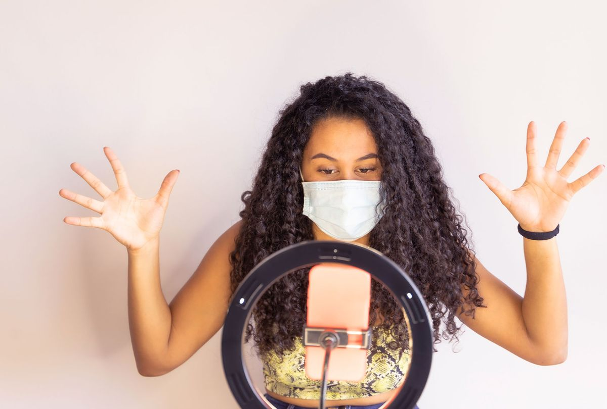 Influencer Girl blogger in medical mask talks about coronavirus (Getty Images)