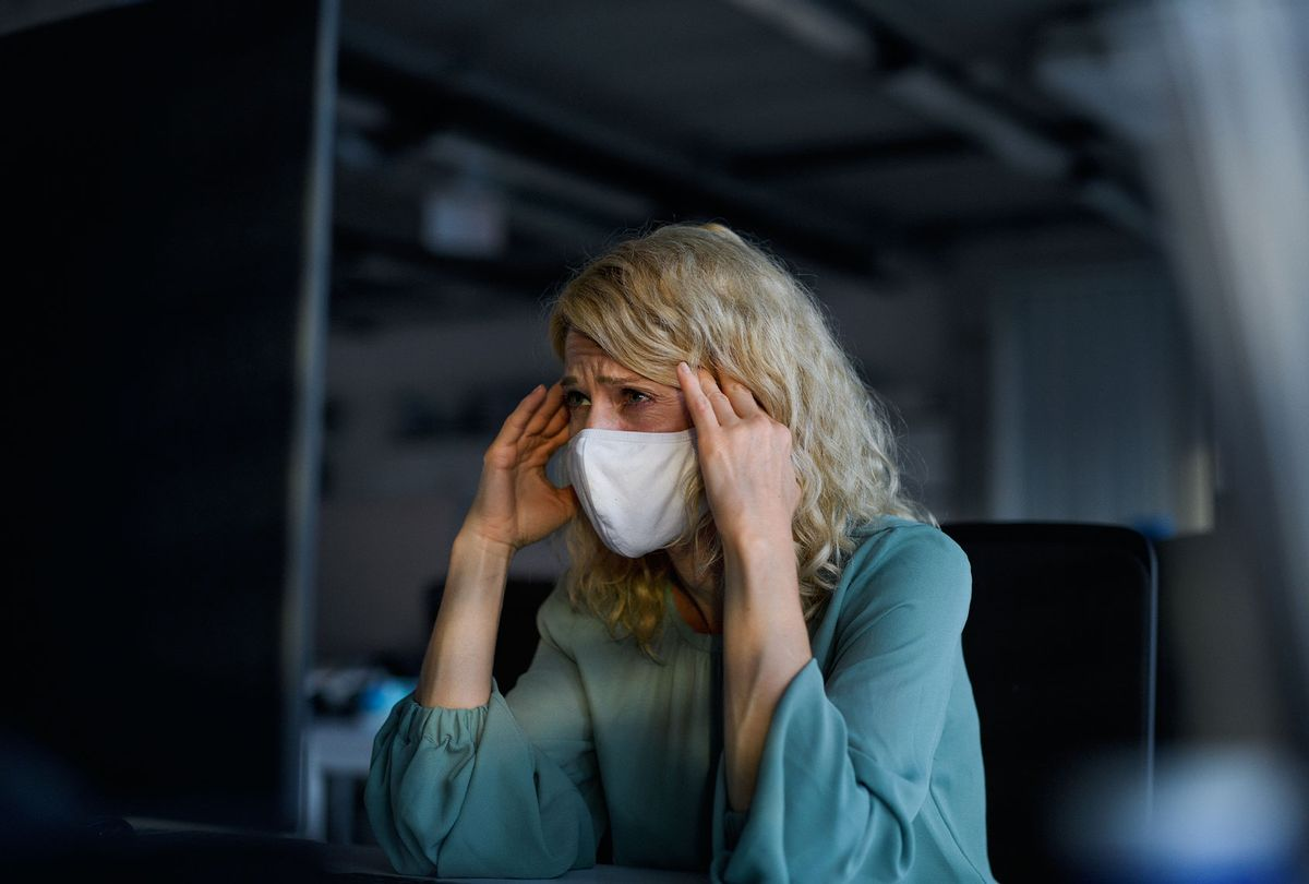 Tired businesswoman with face mask sitting indoors in office, feeling headache (Getty Images)