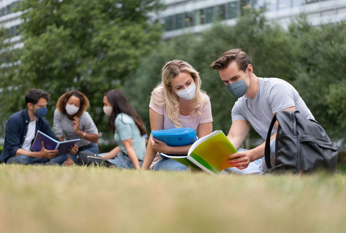 Students wearing face masks while studying outdoors (Getty Images)