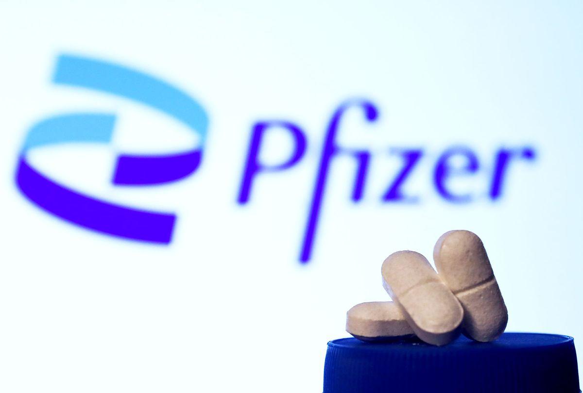 Medicine pills are seen with Pfizer logo displayed on a screen in the background (Jakub Porzycki/NurPhoto via Getty Images)