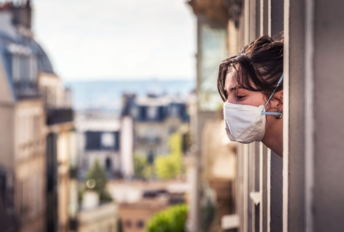 A Parisian girl looks outside the window during the quarantine because the containment of the virus is essential. (Getty Images)