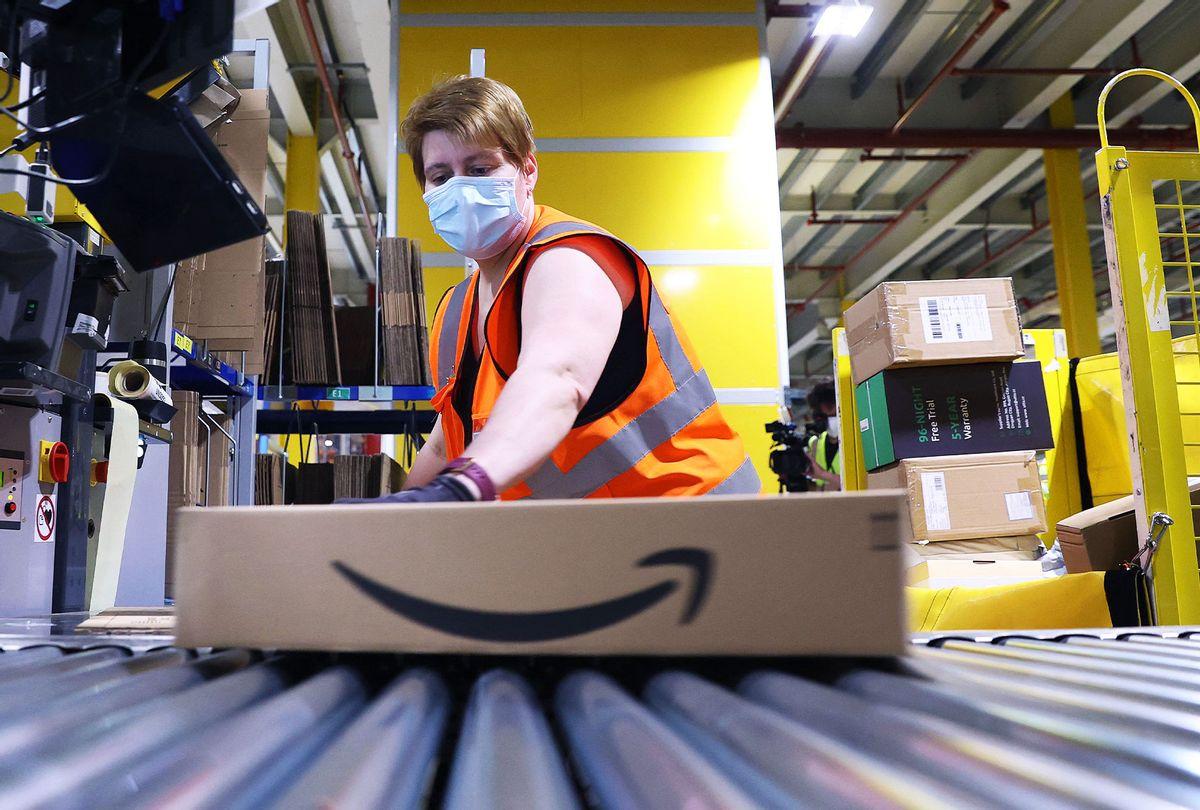 An Amazon employee prepares a package for shipment (RONNY HARTMANN/AFP via Getty Images)