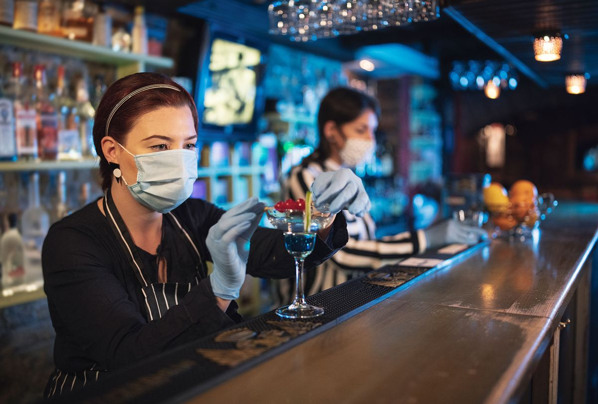 Bartender women working with protective face mask and surgical gloves in night bar. (Getty Images)