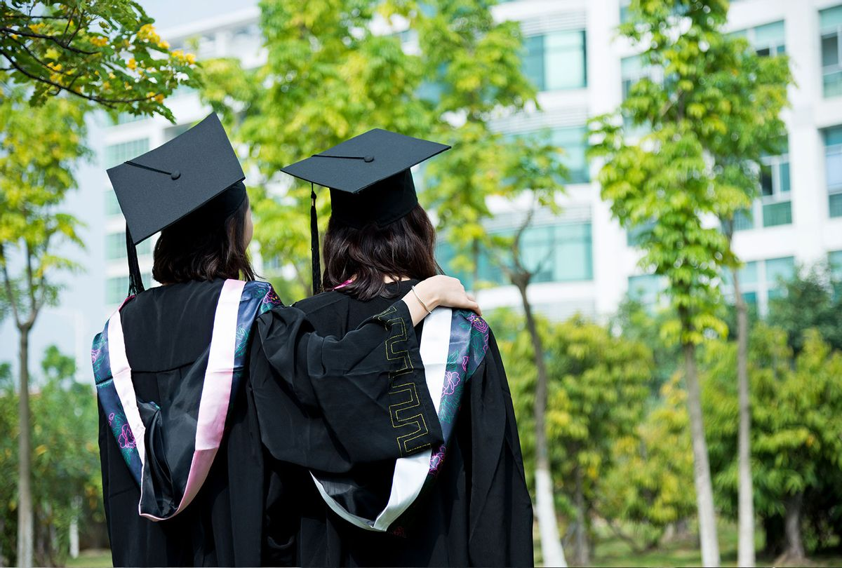 Two college graduates on campus (Getty Images)