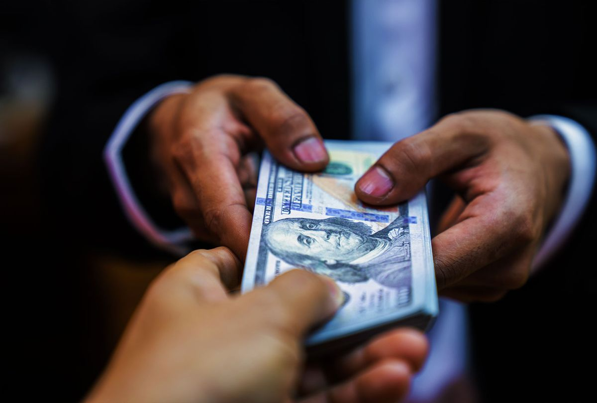 Businessman giving bribe money to partner (Getty Images)