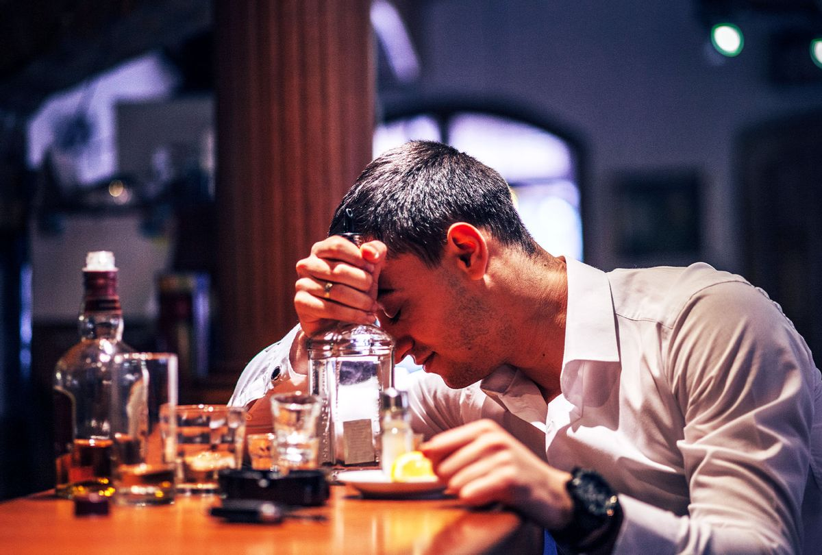 Sad drunk man sitting at counter (Getty Images)