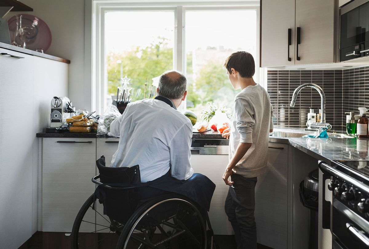 Disabled father preparing food with son in the kitchen (Getty Images)
