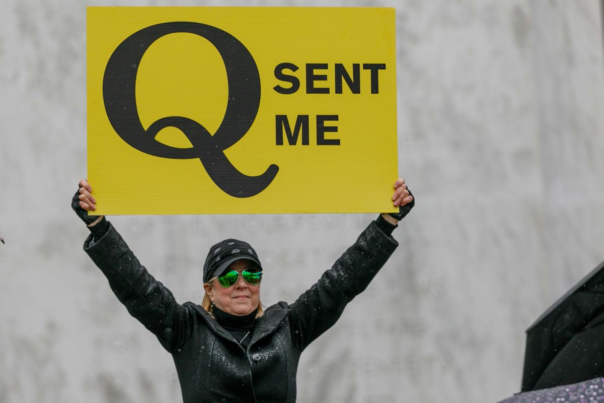A QAnon supporter holds a sign during a protest at the Oregon State Capitol in Salem on May 2, 2020. (Getty Images)