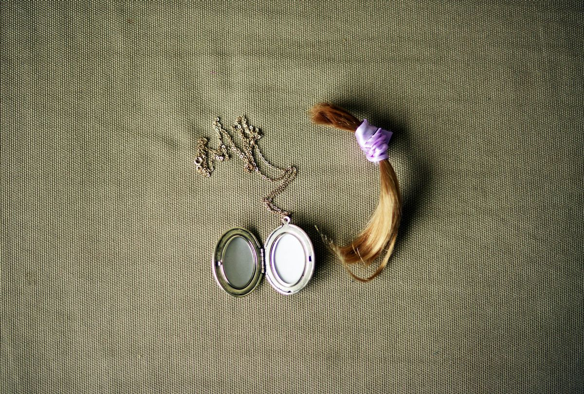 Lock of hair with purple ribbon and a locket necklace (Getty Images)