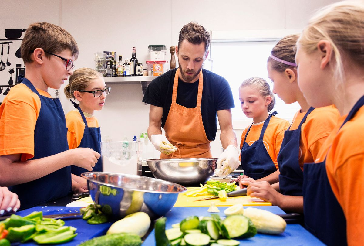 Teacher and students chopping vegetables in cooking class (Getty Images)