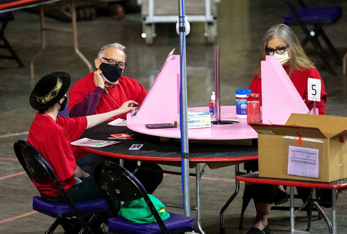 Contractors working for Cyber Ninjas, who was hired by the Arizona State Senate, examine and recount ballots from the 2020 general election at Veterans Memorial Coliseum on May 1, 2021 in Phoenix, Arizona. The Maricopa County ballot recount comes after two election audits found no evidence of widespread fraud. (Courtney Pedroza/Getty Images)