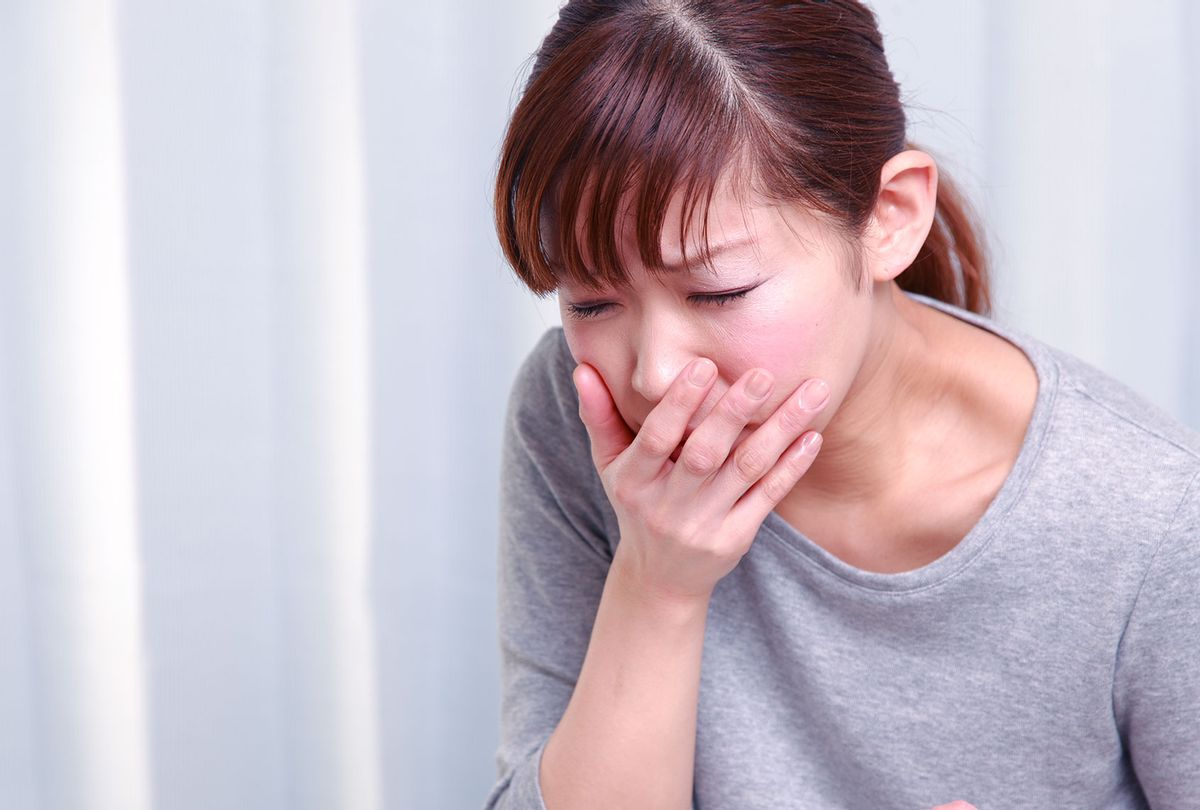 Young woman looking nauseous with hand over mouth (Getty Images)
