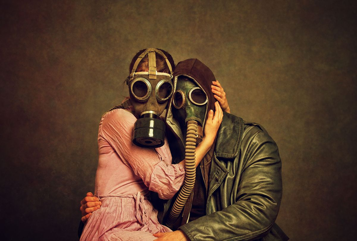 Couple in gas masks embracing (Getty images)