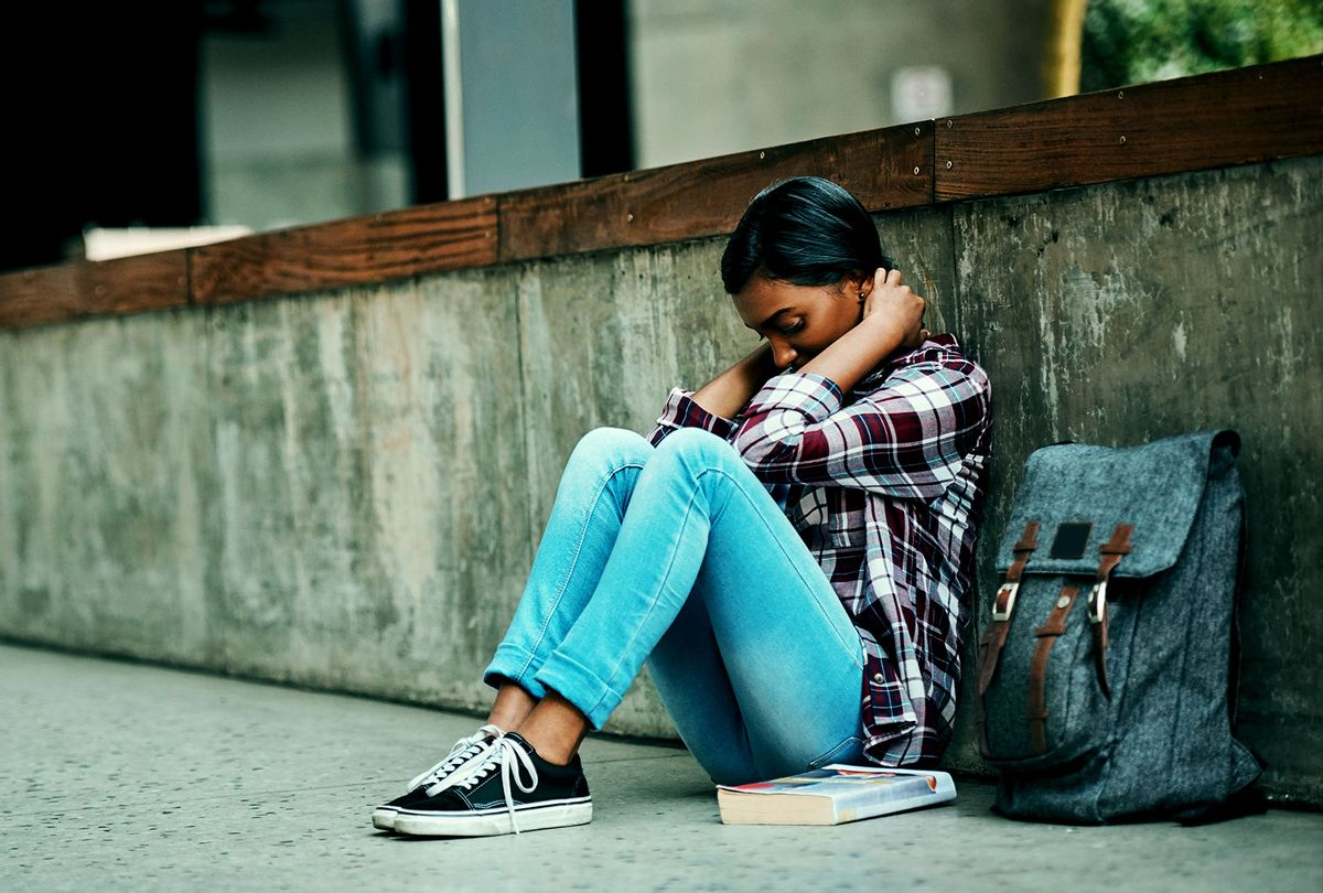 Stressed college student hiding behind a wall (Getty Images)