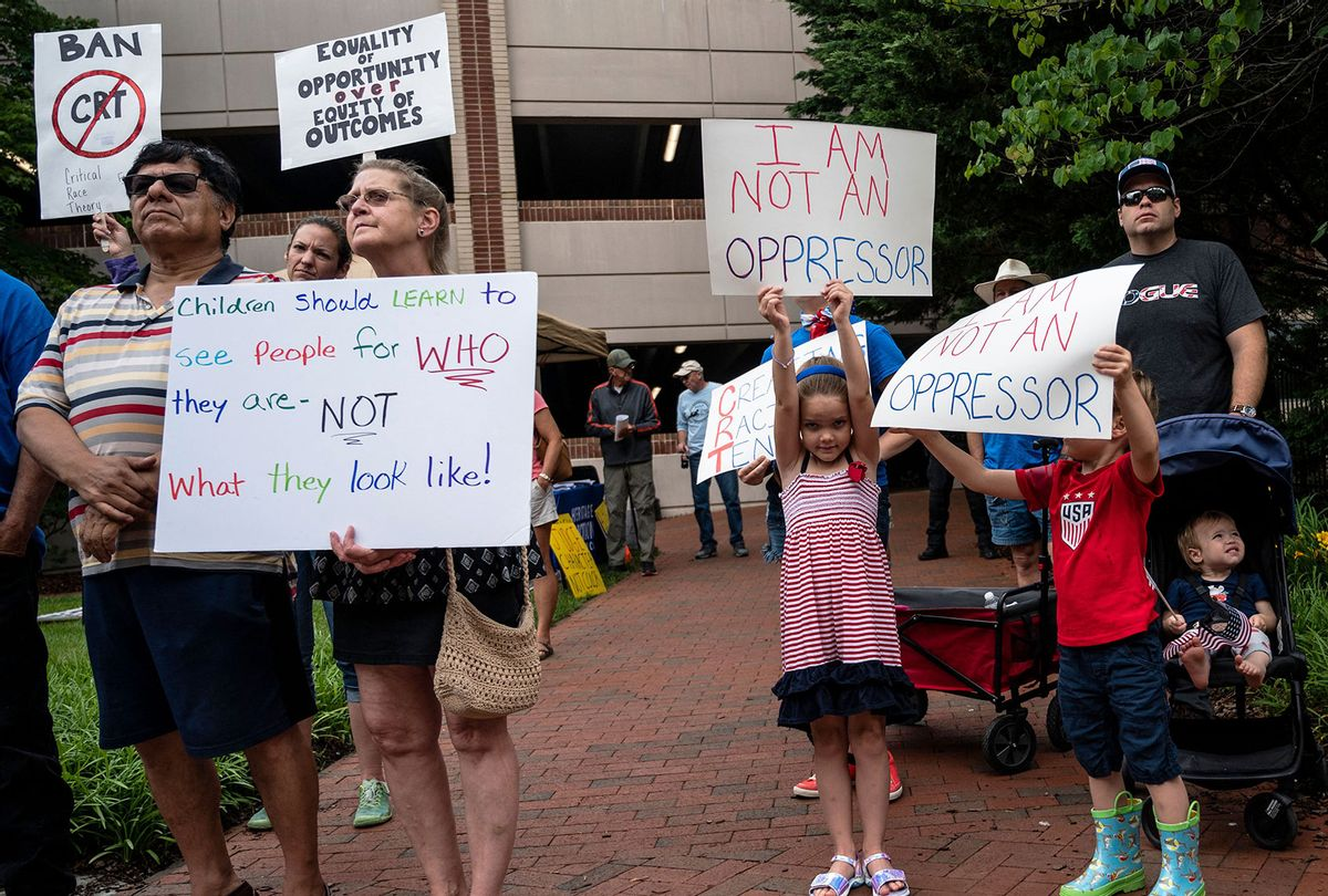 """People hold up signs during a rally against """"critical race theory"""" (CRT) being taught in schools at the Loudoun County Government center in Leesburg, Virginia on June 12, 2021.The term """"critical race theory"""" defines a strand of thought that appeared in American law schools in the late 1970s and which looks at racism as a system, enabled by laws and institutions, rather than at the level of individual prejudices. But critics use it as a catch-all phrase that attacks teachers' efforts to confront dark episodes in American history, including slavery and segregation, as well as to tackle racist stereotypes. (ANDREW CABALLERO-REYNOLDS/AFP via Getty Images)"""