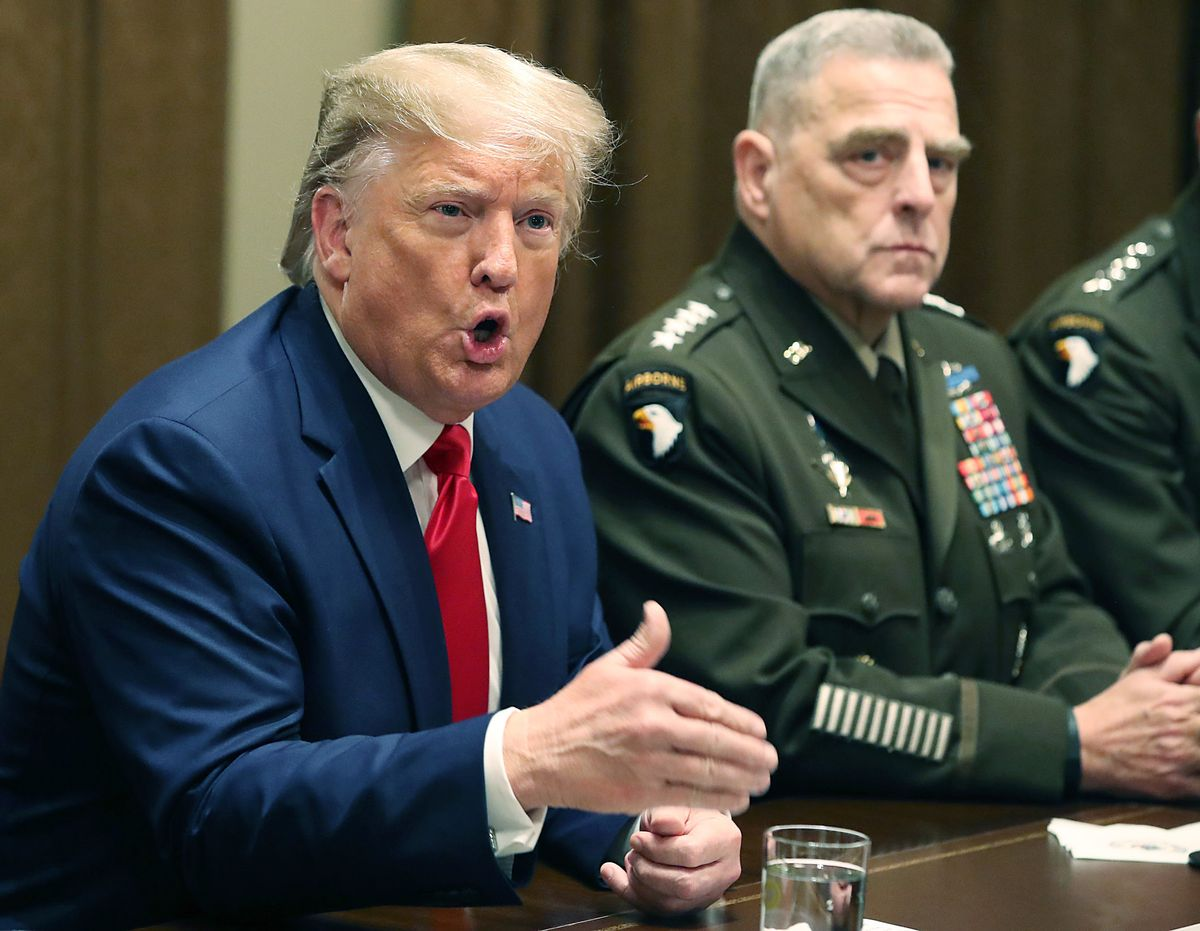 Former President Donald Trump speaks as Joint Chiefs of Staff Chairman, Army General Mark Milley, looks on. (Mark Wilson/Getty Images)
