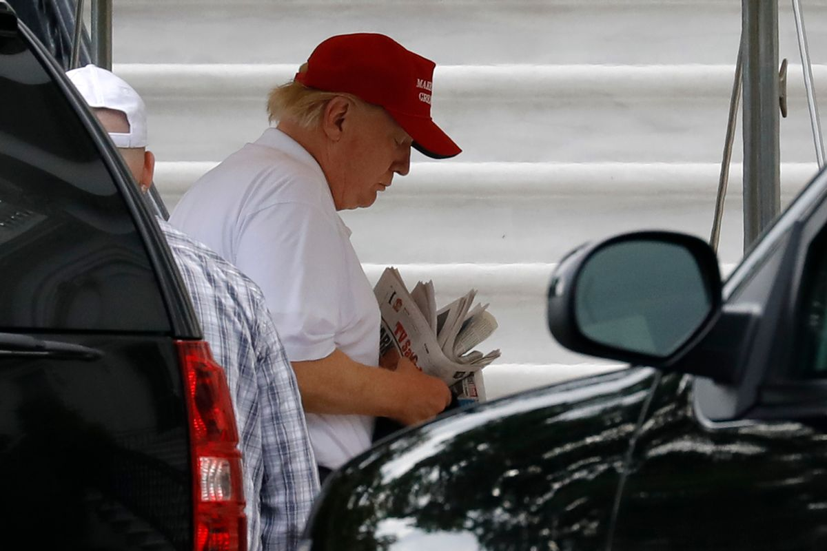 Former President Donald Trump thumbs through a stack of newspapers. (Getty Images)