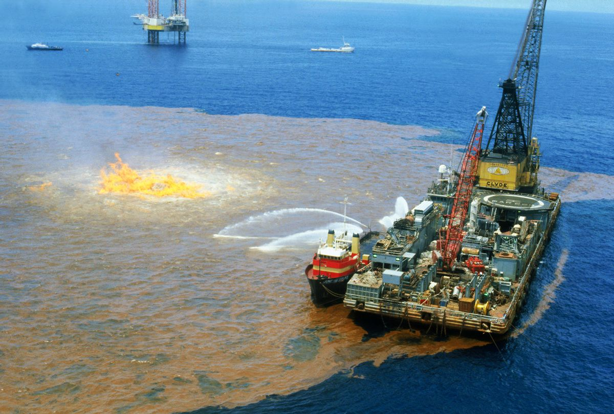 Bay of Campeche, Gulf of Mexico: Workers on barge (right foreground) spray chemical dispersant on excess oil around burning well of the Ixtoc I well here recently. The well continues to gush into the Bay of Campeche, making it the world's largest oil spill. Technicians of Petroleos Mexicanos, the national oil monopoly, last weekend began steadily pumping steel and lead balls--2.5 to 2.7 inches in diameter---into the blown out Ixtoc I well to help lessen the spillage. Through 8/11, Ixtoc I had spewed about 1.81 million barrels of oil into the bay, company officials said. (Getty Images)
