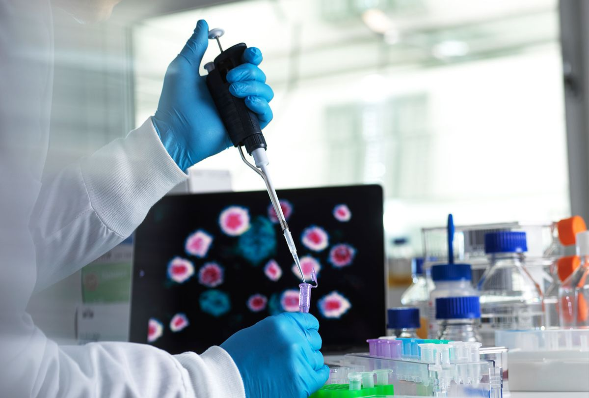 Scientist pipetting a sample of a new drug formula into a vial during a clinical trial with the infectious disease on the computer screen. (Getty Images)