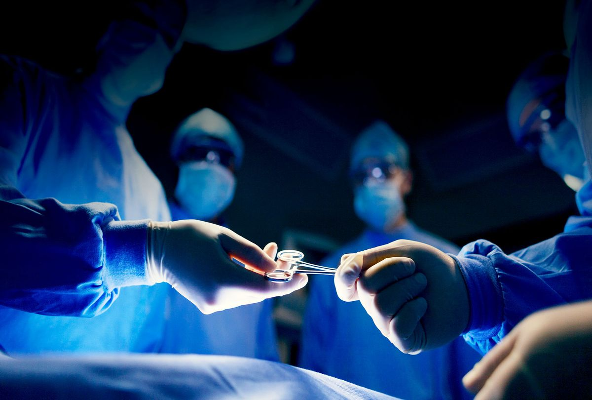 Operating room staff performing hospital surgery (Getty Images/Shannon Fagan)