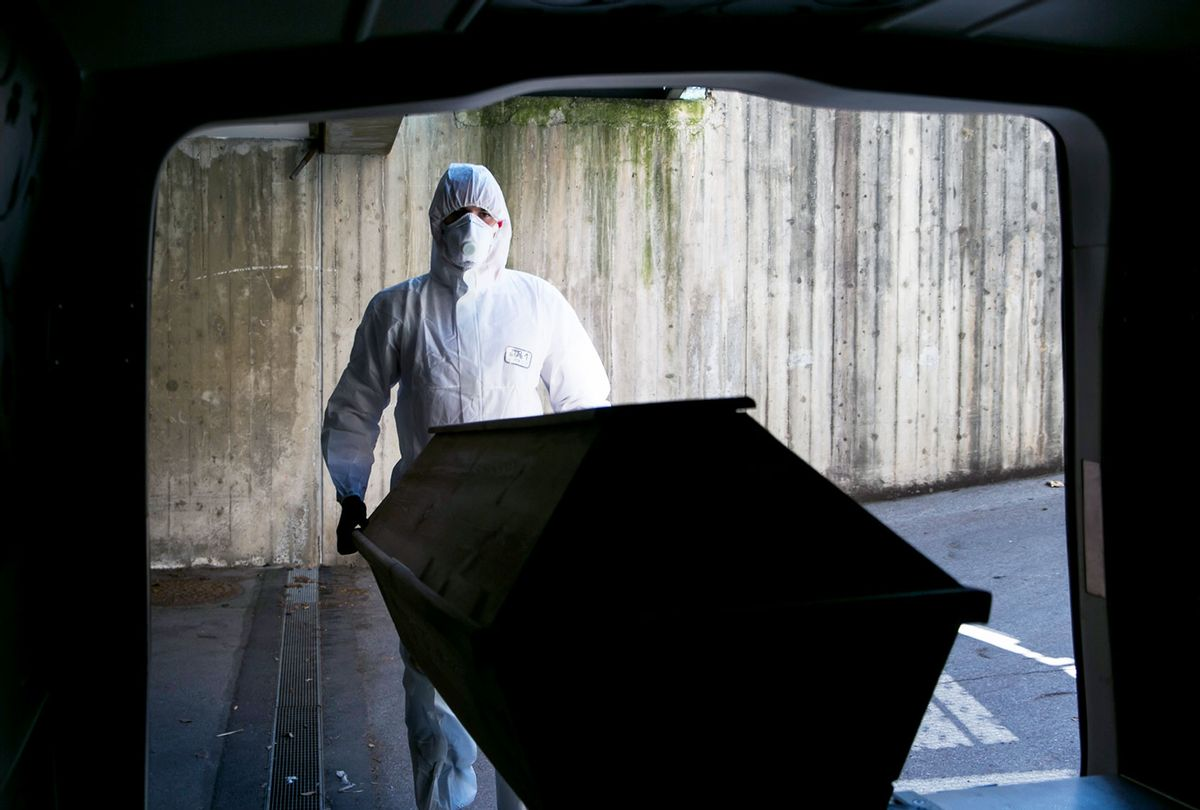 Undertaker worker dressed in full protective clothing and mask pushes a coffin carrying a deceased Covid-19 victim into a mortuary van at a morgue on April 2, 2020. (Jan Hetfleisch/Getty Images)