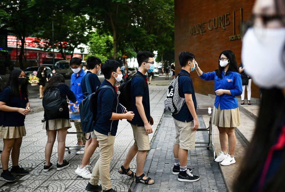 Students wearing face masks stand in a queue to get their temperatures checked at the Marie Curie school in Hanoi on May 4, 2020, as schools re-opened after a three-month closure to combat the spread of the COVID-19 novel coronavirus. (MANAN VATSYAYANA/AFP via Getty Images)