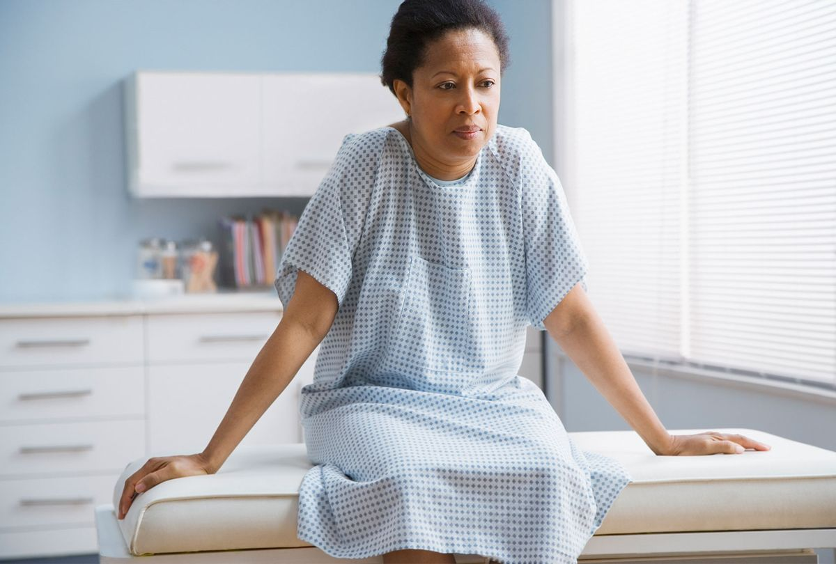Woman patient sitting on examination table in doctor's office (Getty Images)