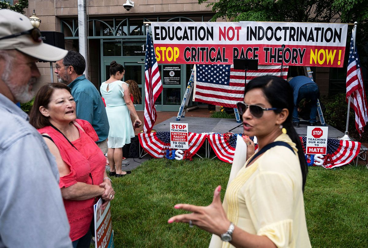 """People hold up signs during a rally against """"critical race theory"""" (CRT) being taught in schools at the Loudoun County Government center in Leesburg, Virginia on June 12, 2021. The term """"critical race theory"""" defines a strand of thought that appeared in American law schools in the late 1970s and which looks at racism as a system, enabled by laws and institutions, rather than at the level of individual prejudices. But critics use it as a catch-all phrase that attacks teachers' efforts to confront dark episodes in American history, including slavery and segregation, as well as to tackle racist stereotypes. (ANDREW CABALLERO-REYNOLDS/AFP via Getty Images)"""