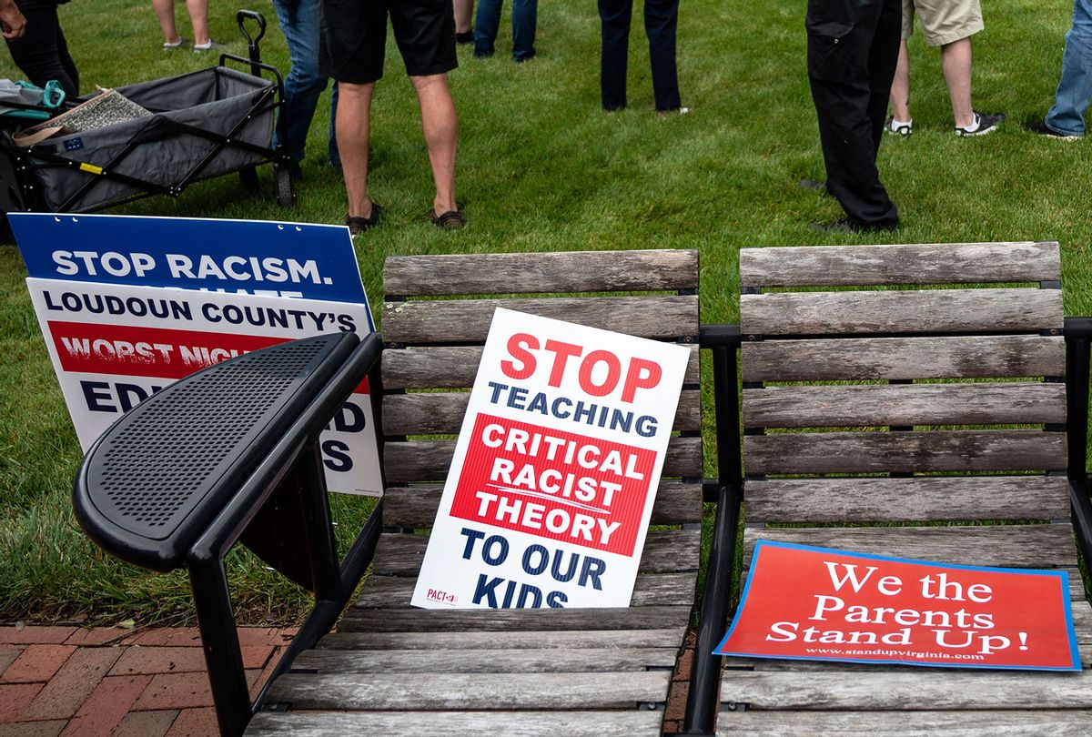 """Signs are seen on a bench during a rally against """"critical race theory"""" (CRT) being taught in schools at the Loudoun County Government center in Leesburg, Virginia on June 12, 2021. (ANDREW CABALLERO-REYNOLDS/AFP via Getty Images)"""
