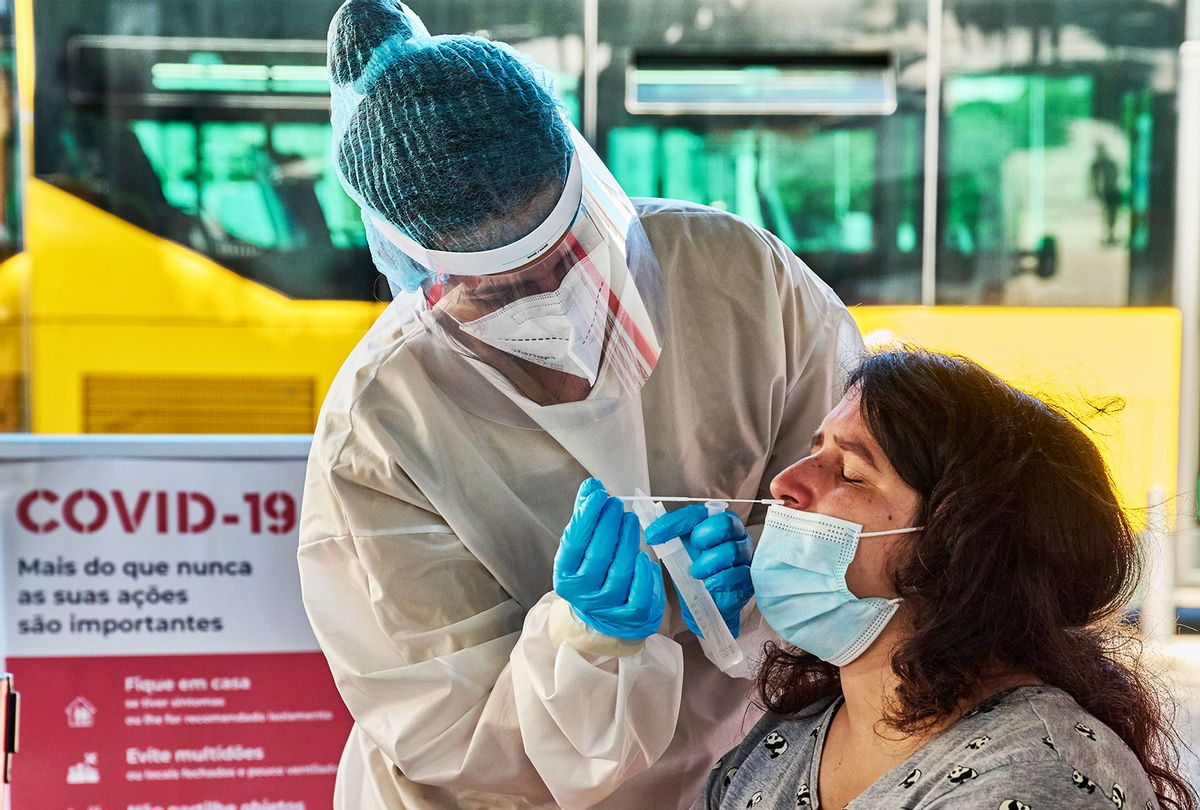 Health technician clad in full protective equipment performs a nasal swab for the antigen COVID-19 test (Horacio Villalobos/Getty Images)