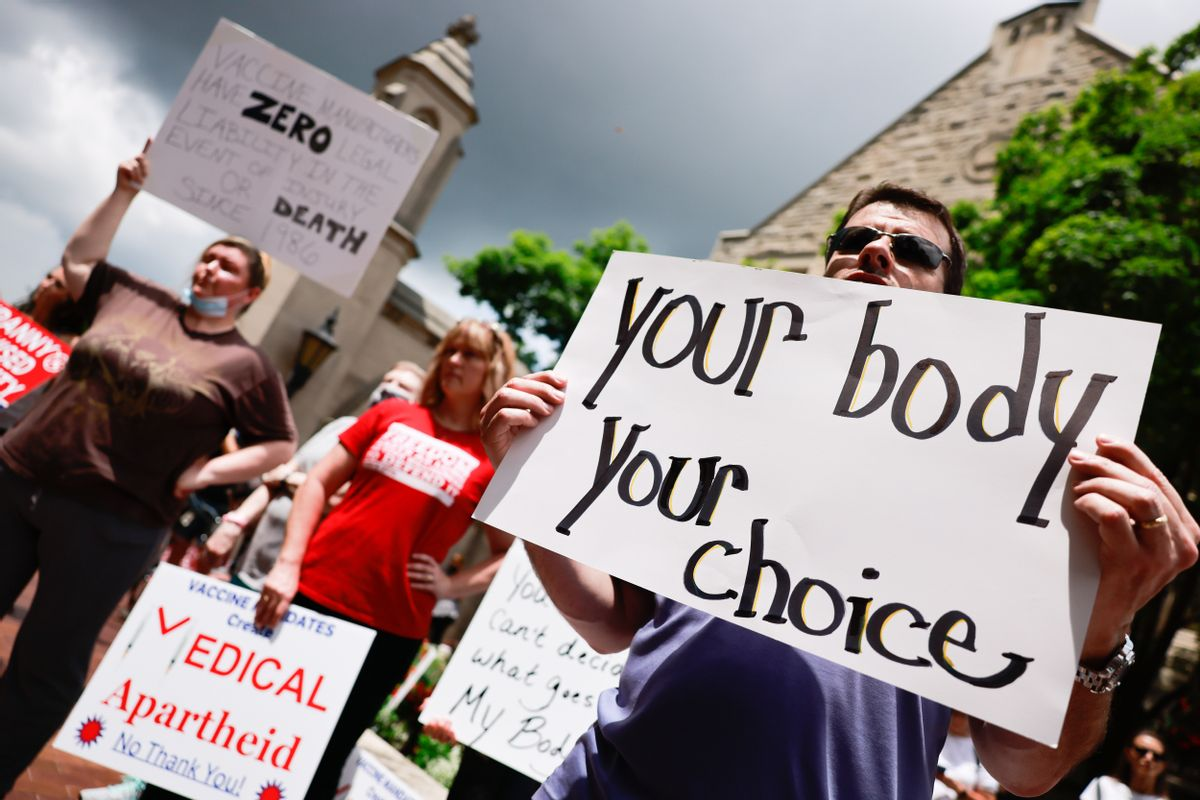 Protesters holding placards gather at Indiana University's Sample Gates during an anti-vaccine demonstration. (Jeremy Hogan/SOPA Images/LightRocket via Getty Images)
