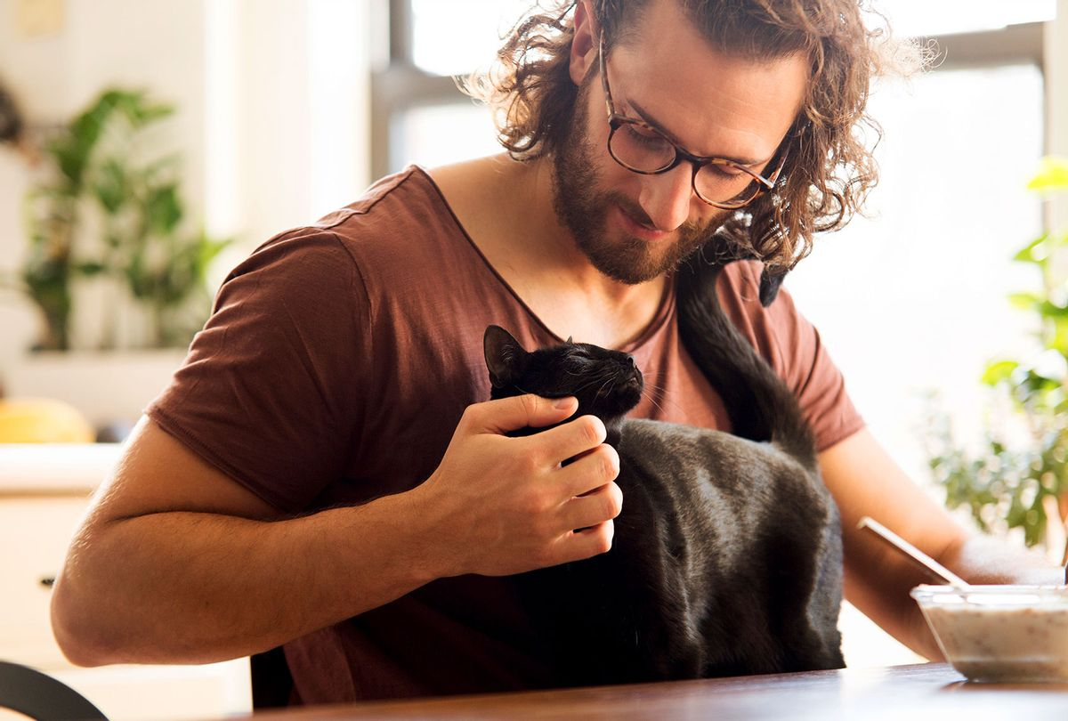 Young man stroking his black cat (Getty Images)