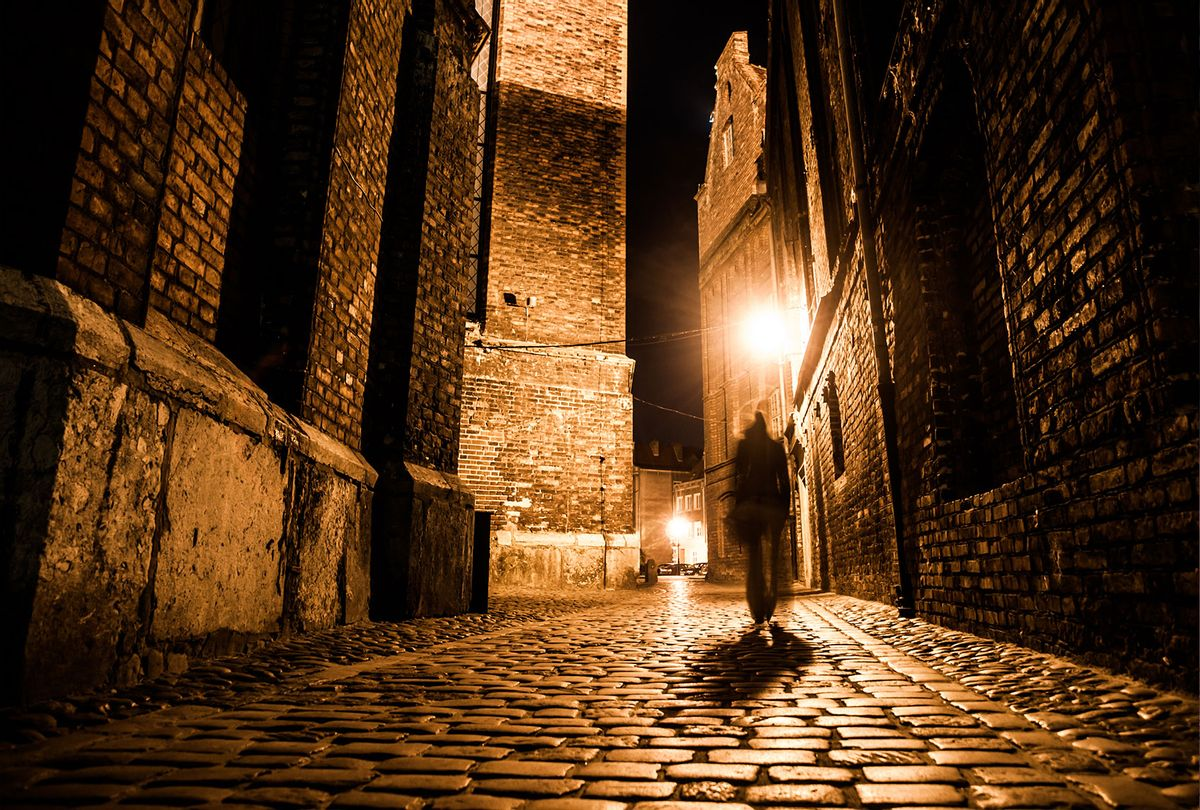 Illuminated cobbled street in old city by night (Getty Images/Pyty Czech)