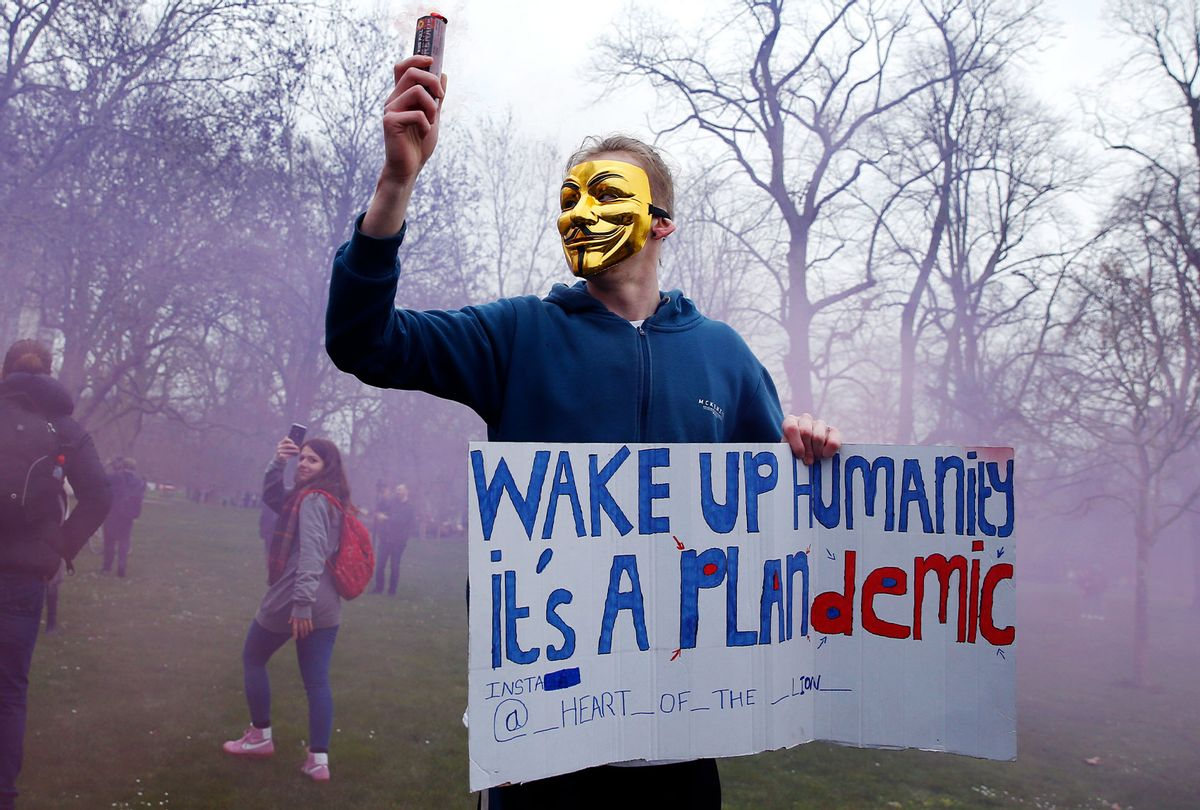 """A protester with a flare poses holding a sign calling for people to """"wake up"""" during a """"World Wide Rally For Freedom"""" protest, a QAnon adjacent conspiracy-theory movement. (Hollie Adams/Getty Images)"""