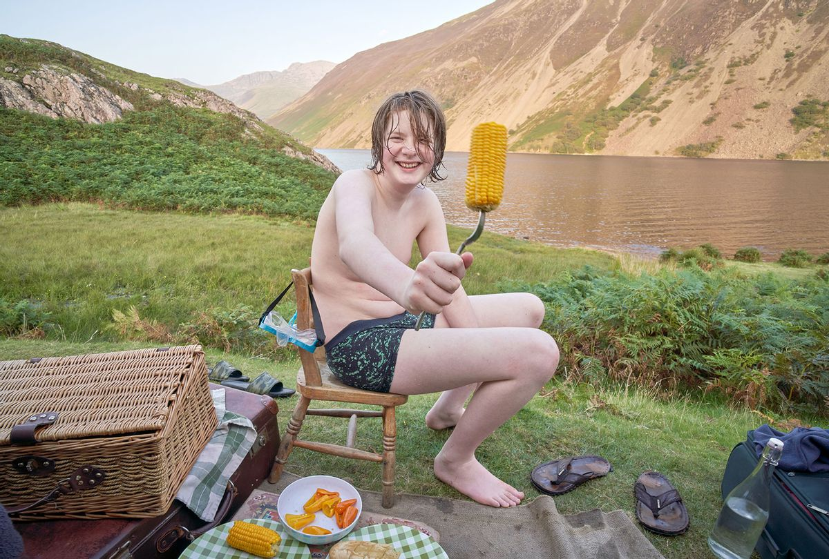 A teenage boy enjoying corn after swimming (Getty Images/Roy JAMES Shakespeare)
