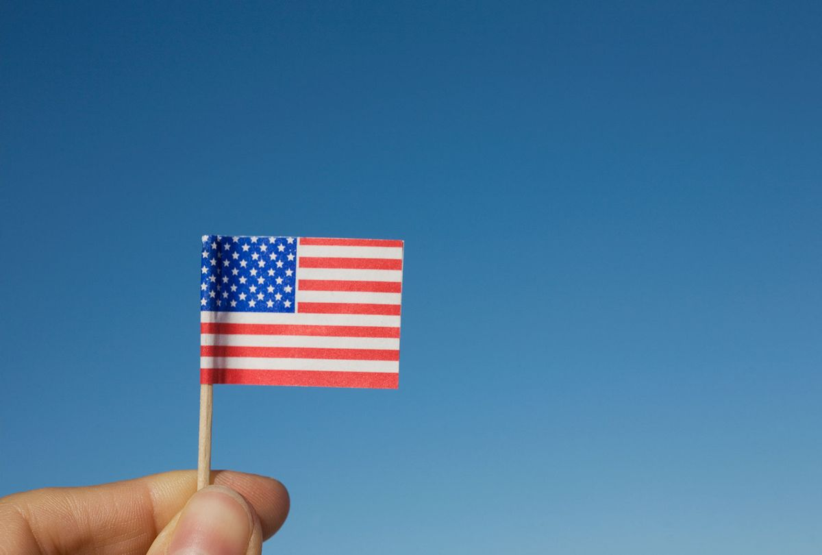 Hand holding small American flag (Getty Images/David Engelhardt)