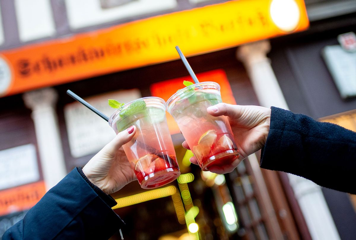 Two friends toast with to-go strawberry mojitos in front of a bar. (Hauke-Christian Dittrich/picture alliance via Getty Images)