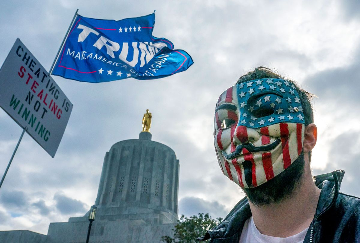 A protester in a Guy Fawkes mask stands in front of the Oregon State Capitol building during a Stop the Steal rally in Salem, Oregon. Angry supporters of President Trump took to the streets across the country following reporting that President-elect Joe Biden had won the election. (Nathan Howard/Getty Images)