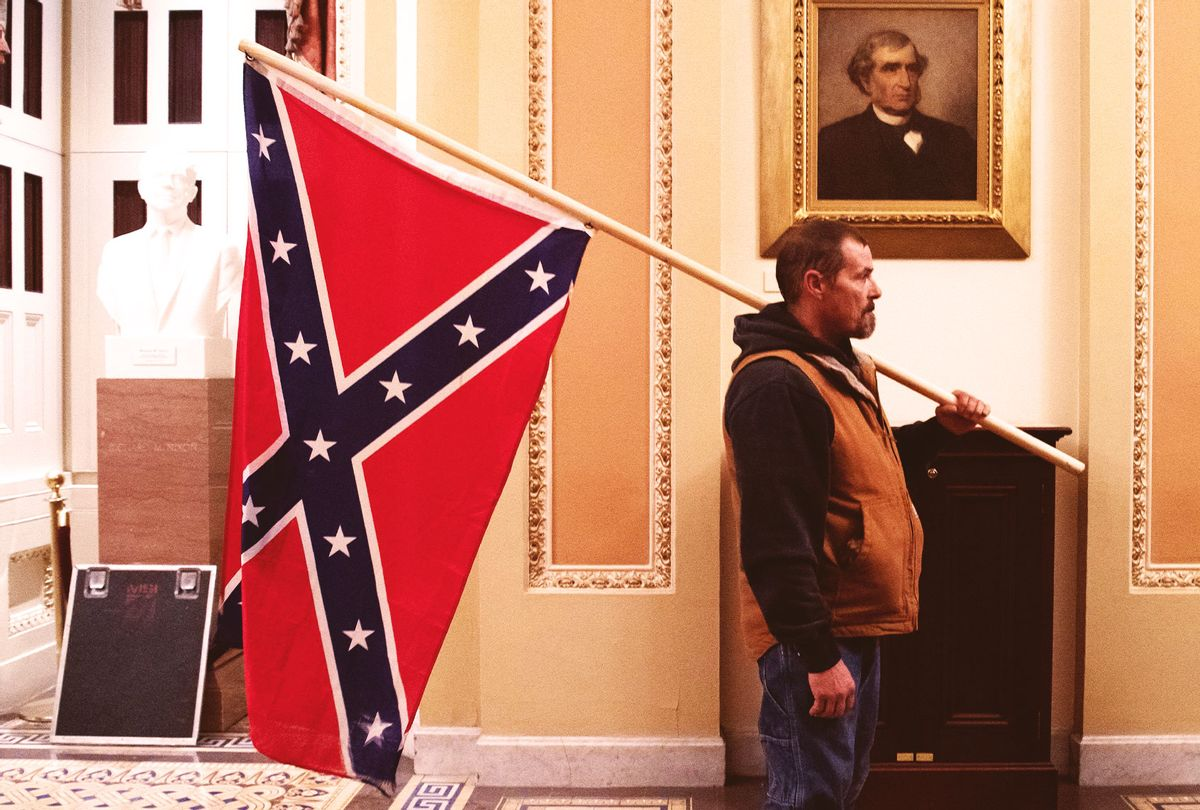 A supporter of US President Donald Trump holds a Confederate flag outside the Senate Chamber during a protest after breaching the US Capitol in Washington, DC, January 6, 2021. - The demonstrators breeched security and entered the Capitol as Congress debated the 2020 presidential election Electoral Vote Certification. (SAUL LOEB/AFP via Getty Images)