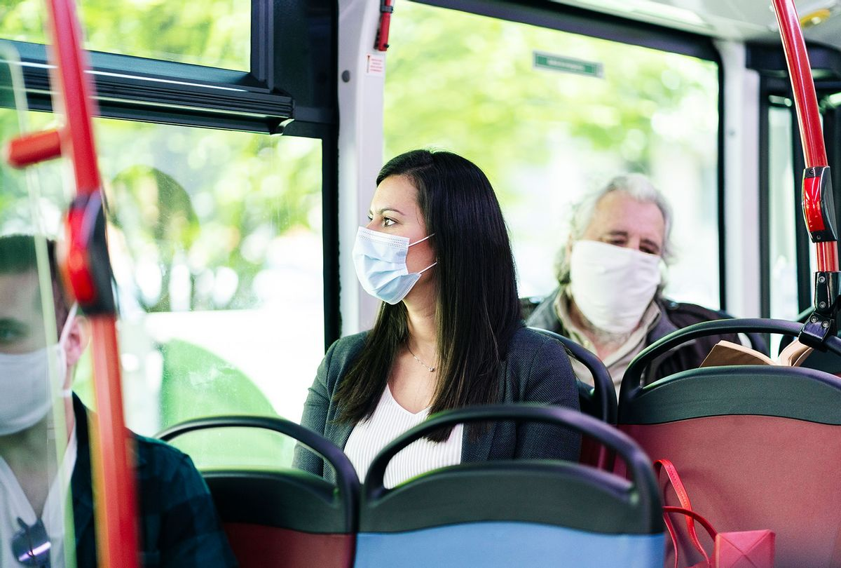 Woman wearing protective mask sitting in bus (Getty Images)