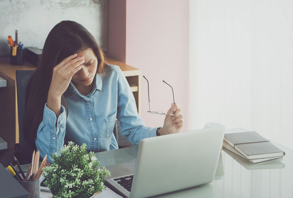 Stressed Woman By Laptop On Table (Getty Images/Bundit Binsuk)